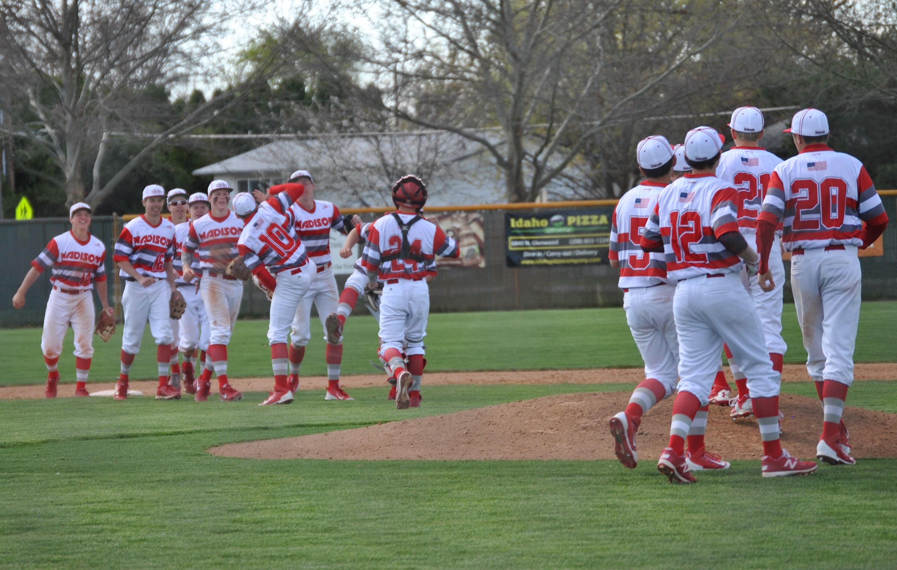 Madison's varsity team celebrating in style after Matt Bolingbroke threw a complete game against Capital in Boise. Courtesy photo: Ginger Crawford