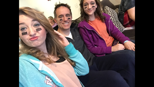 Sophomore Stephanie Stumpf and Freshman Savanna White waiting for the 2015 Super Bowl to start with their dad. Photo Courtesy Savanna White