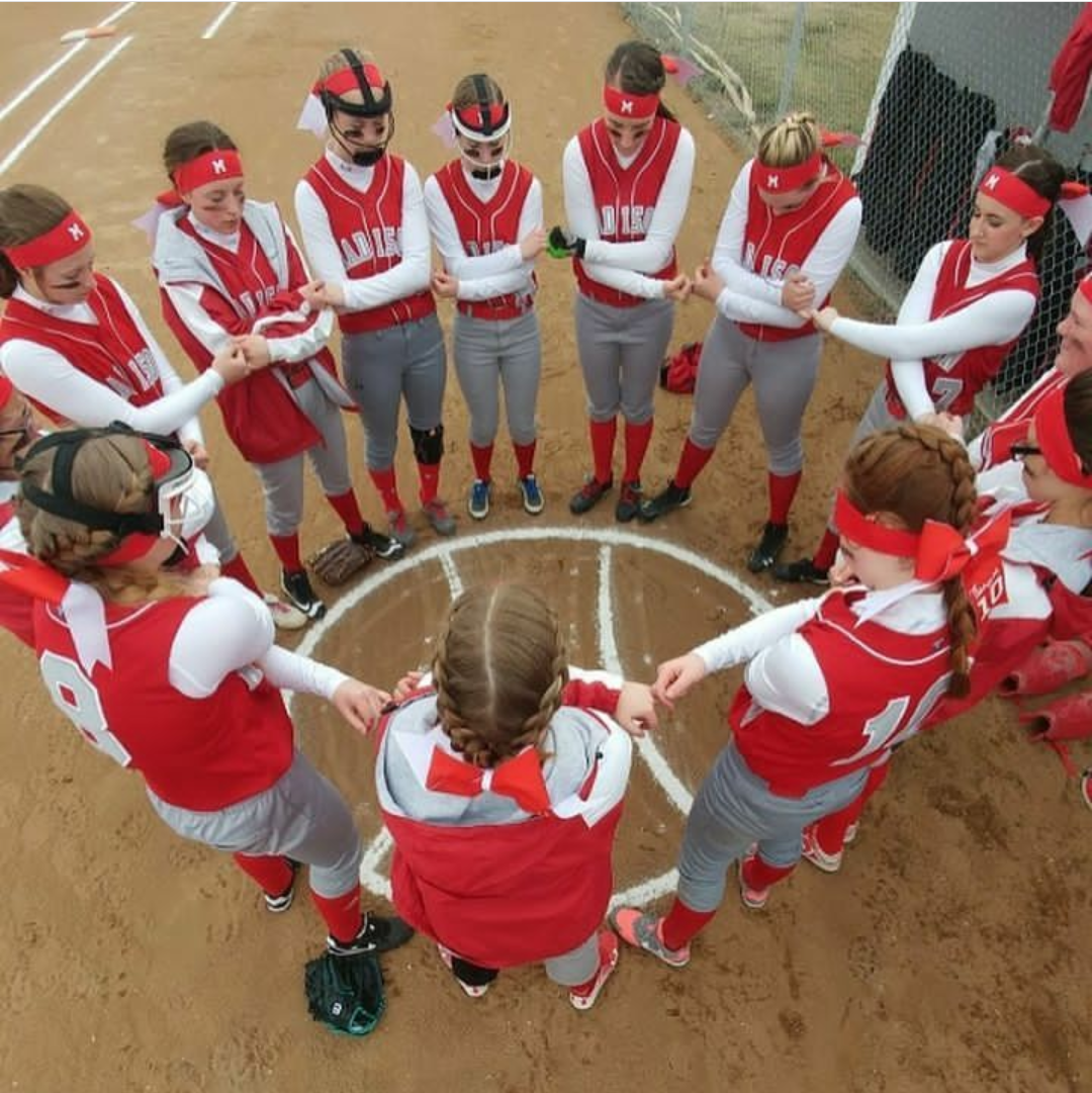 The softball team forms a circle to come together before their game.  Photo Courtesy of Eden Little