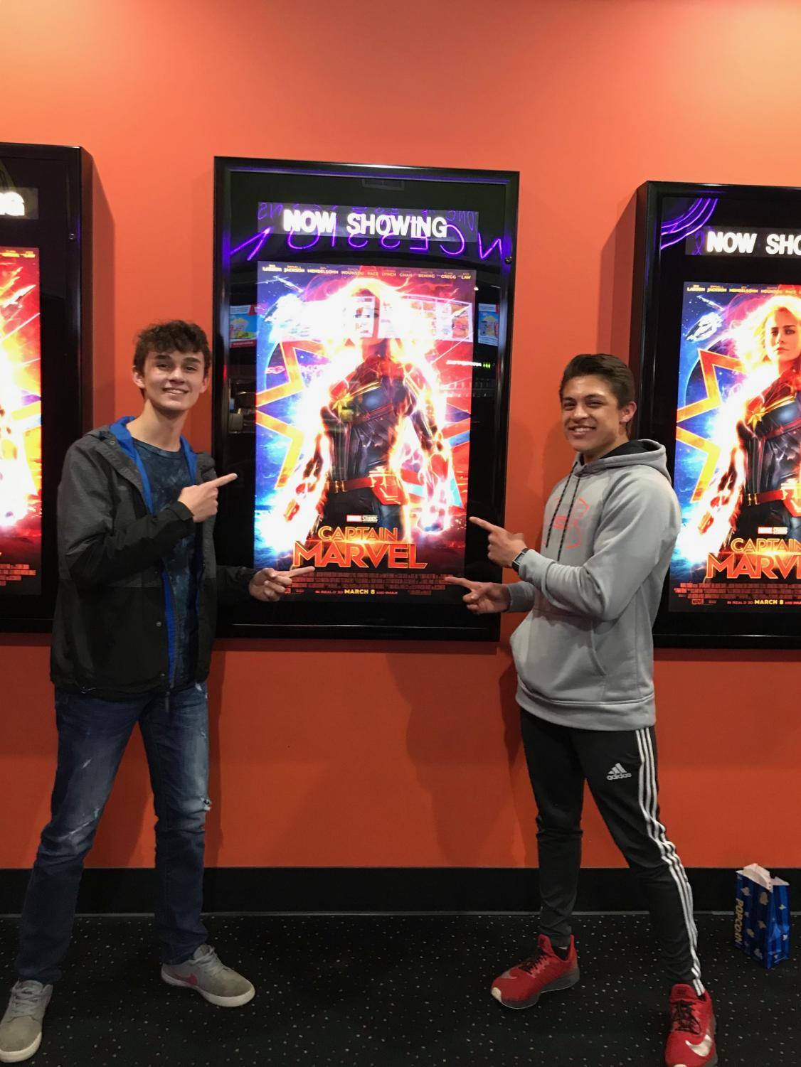 Junior Alex Rasmussen and Junior Chance Sleight standing in front of the Captain Marvel poster.