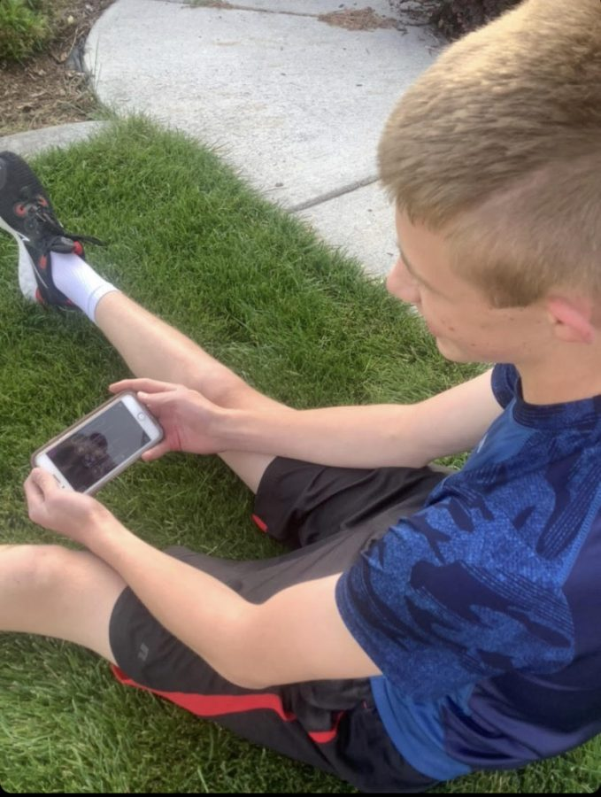 Traven outside playing 'Among Us' on his phone