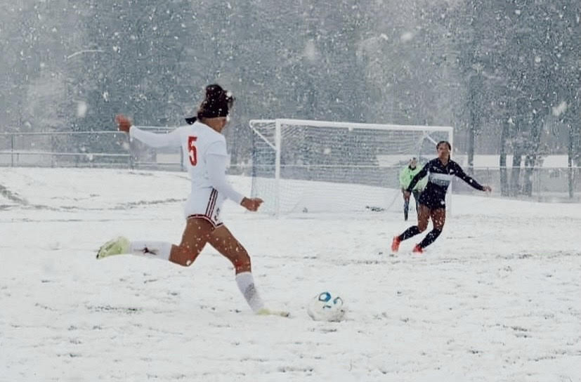 The girls' soccer team playing in the snow on Friday afternoons game.