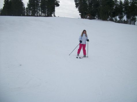 A student skiing down a snowy hill