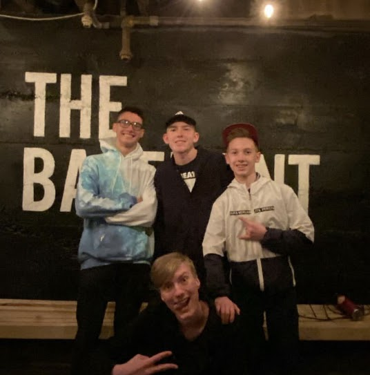Meshke and his band members posing in front of The Basement