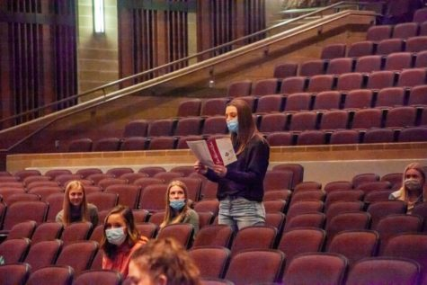 Singing in masks is the new normal for choir students during Covid. So is social distancing in the auditorium instead of the choir room.