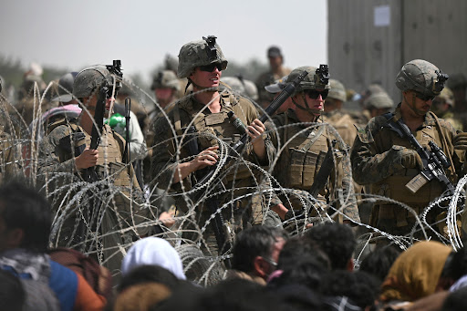 U.S. soldiers guarding behind barb wired fence as Afghans sit near the airport in Kabul, Afghanistan. Afghans hoping to flee the country after the Taliban takes over Afghanistan.