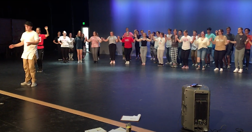 The whole cast practicing the tradition dance while at rehearsal.