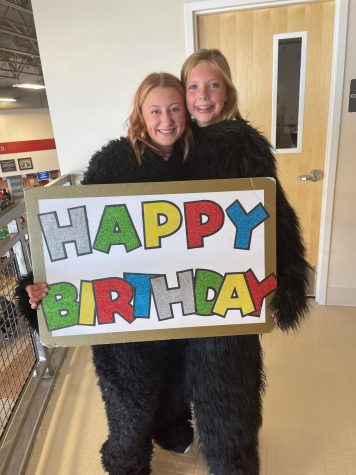 Pierce and Cazier holding a happy birthday sign for McClure.