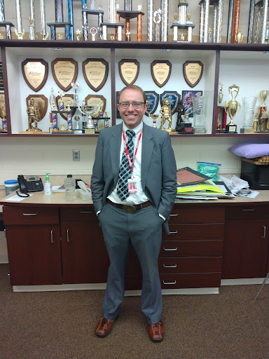 Willford in front of the trophies his teams have won over the years. Willford is the debate coach for MHS.